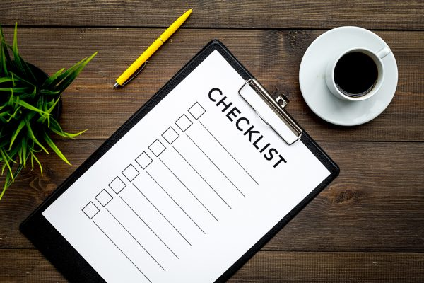Blank checklist with space for ticks on pad on office desk. Checklist for office worker, manager, businessman, chief on dark wooden background top view.